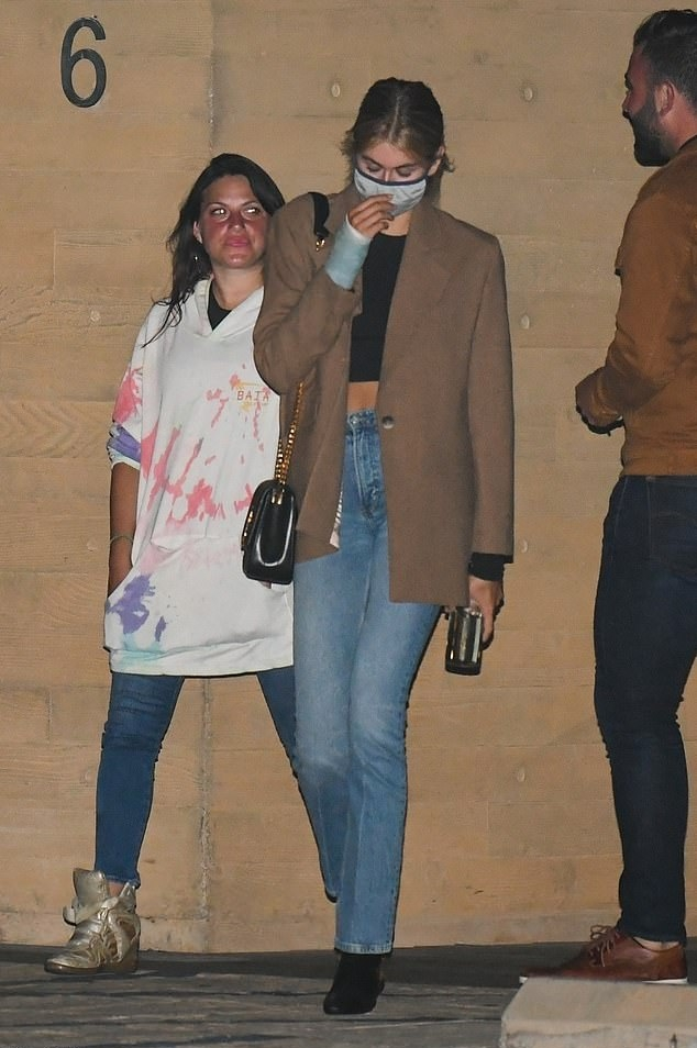 Kaia Gerber wearing narrow black leather boots by BY FAR with pointy heel