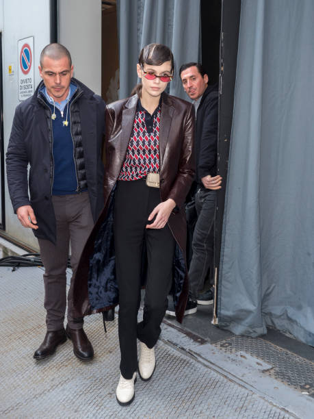 Kaia Gerber, red shirt, dark brown trench coat, white boots, button front, shirt collar, tucked in, black trousers, beige waist bag, patterned print, red sunglasses, printed. Kaia Gerber wearing a red tucked in shirt with shirt collar and button front
