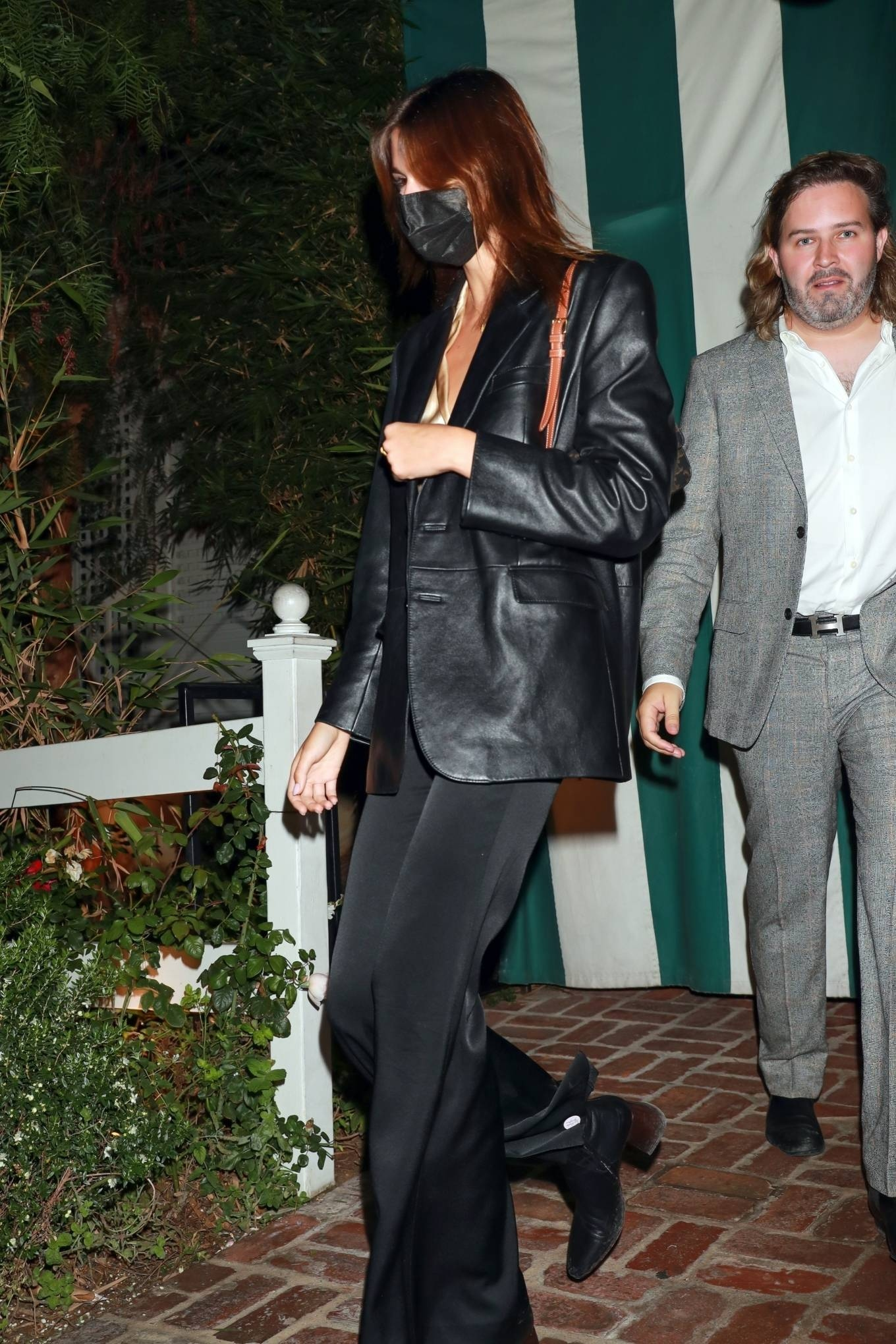 Kaia Gerber wearing tapered toe black boots with flat heel