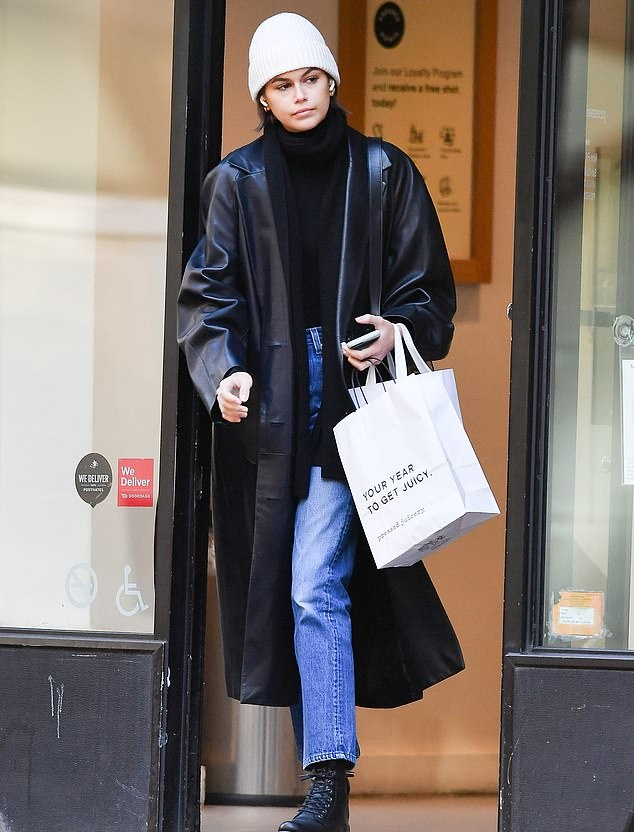 Kaia Gerber donning a oversized black button front leather trench coat with extra long sleeves and peak lapel collar
