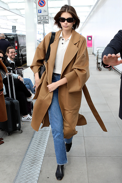 Kaia Gerber rocking a white tucked in shirt with shirt collar and button front
