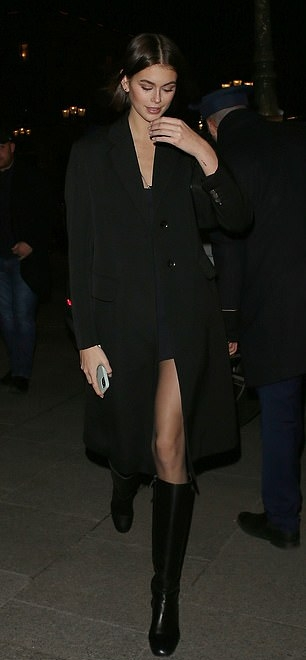 Kaia Gerber donning a black button front coat with full sleeves, peak lapel collar and flap pockets
