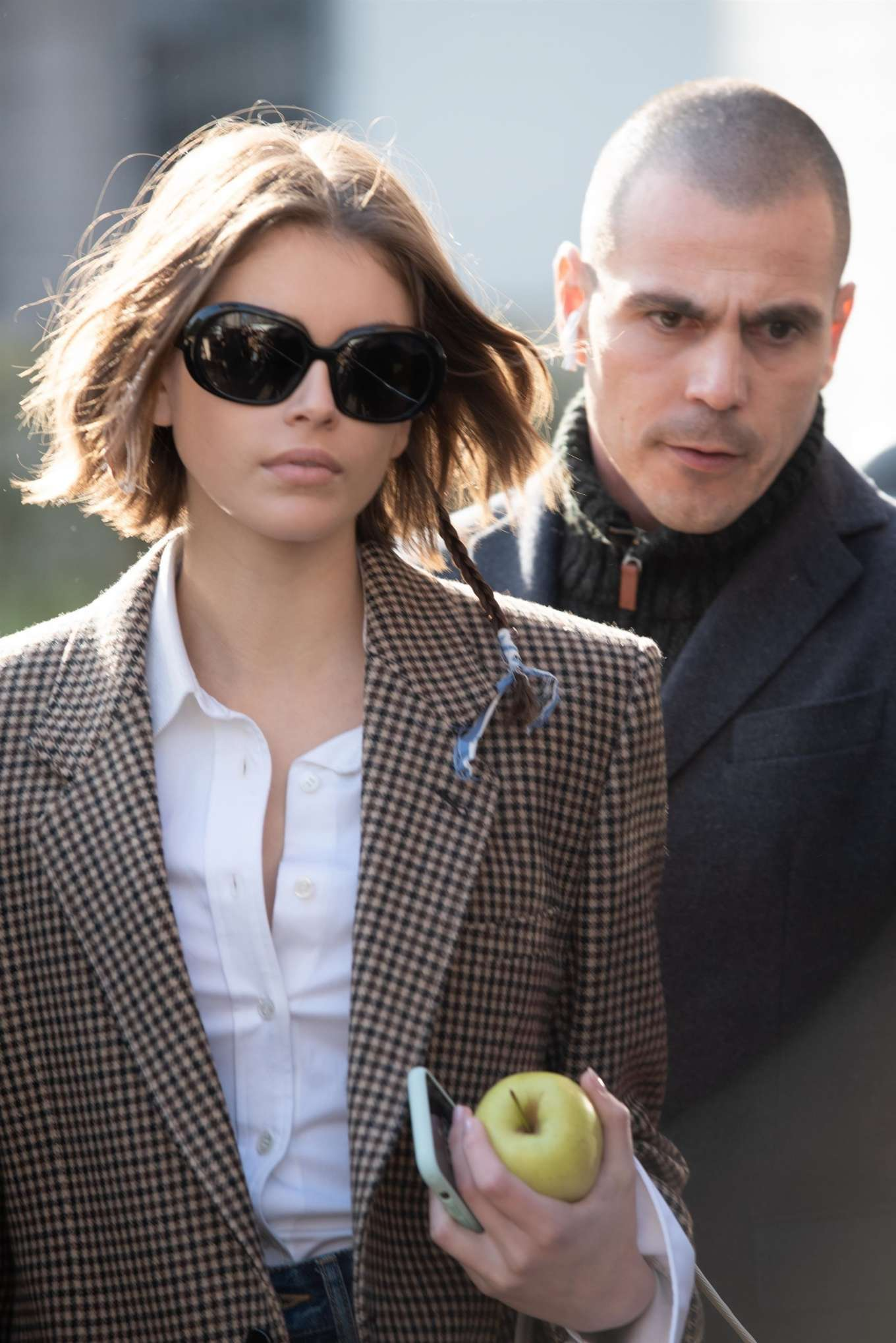 Kaia Gerber rocking a white tucked in shirt with full sleeves, shirt collar and button front