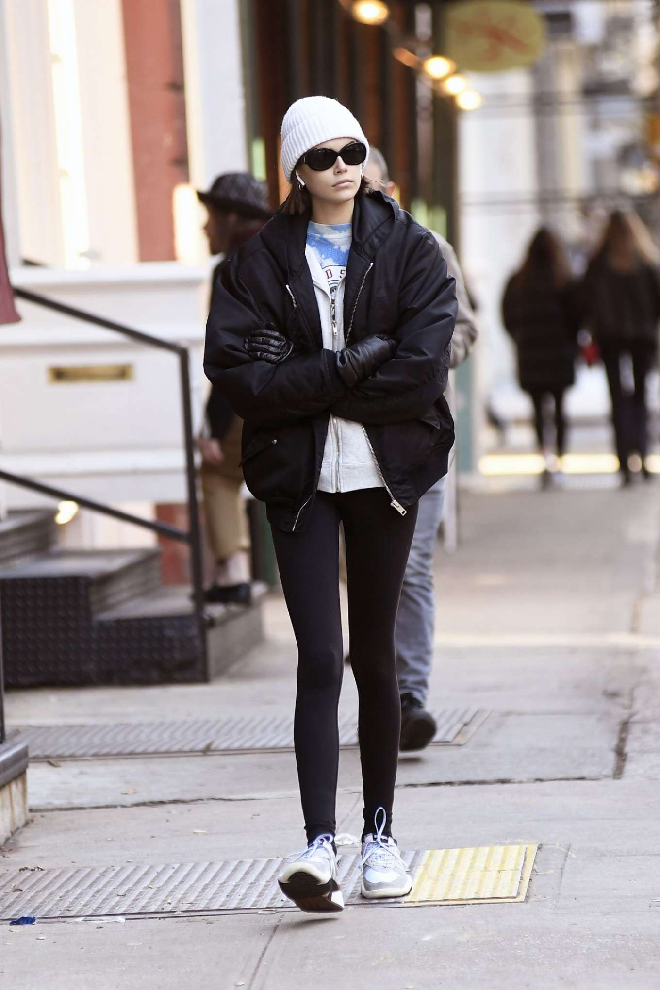 Kaia Gerber donning striped grey Adidas lace-up trainers