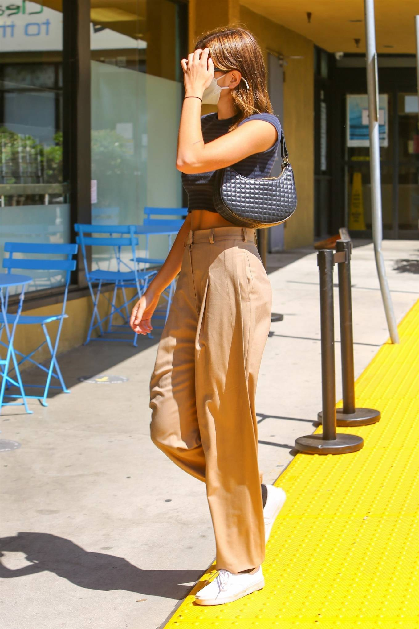 Kaia Gerber wearing relaxed fit beige high waist trousers