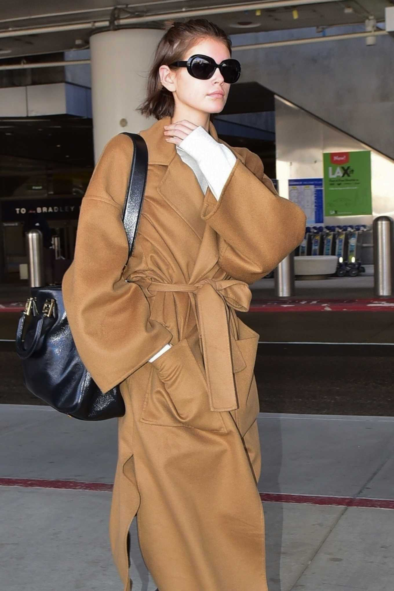 Kaia Gerber rocking a Oversized camel knotted design cashmere trench coat with a cashmere material, extra long sleeves, peak lapel collar, knotted and cinched waist