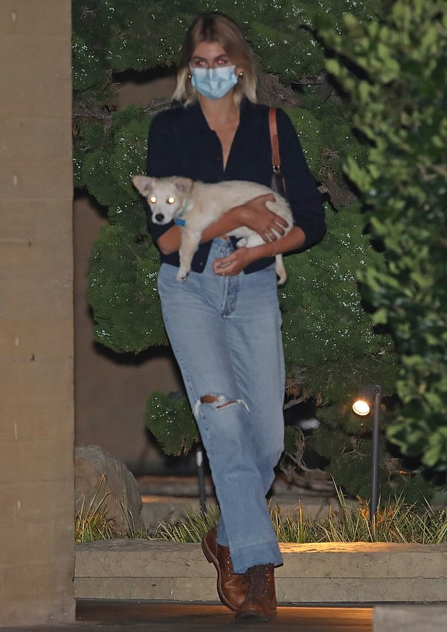 Kaia Gerber donning a navy blue button front shirt with rolled sleeves and shirt collar