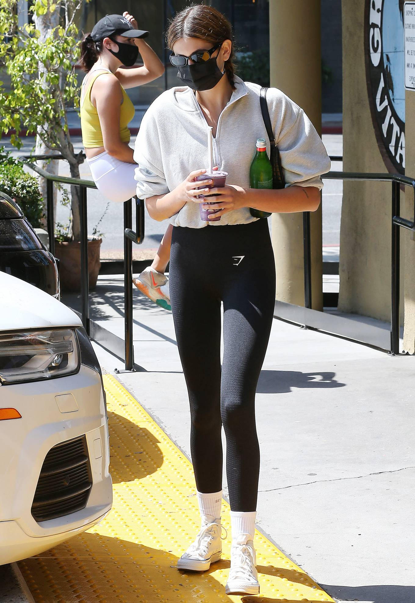 Kaia Gerber, white  canvas shoes, Converse  canvas shoes, black Celine shoulder bag, oversized off white sweater, flat heel, canvas, round, ankle, black Ray Ban sunglasses, figure hugging black Gymshark workout leggings, brand logo, lace-up