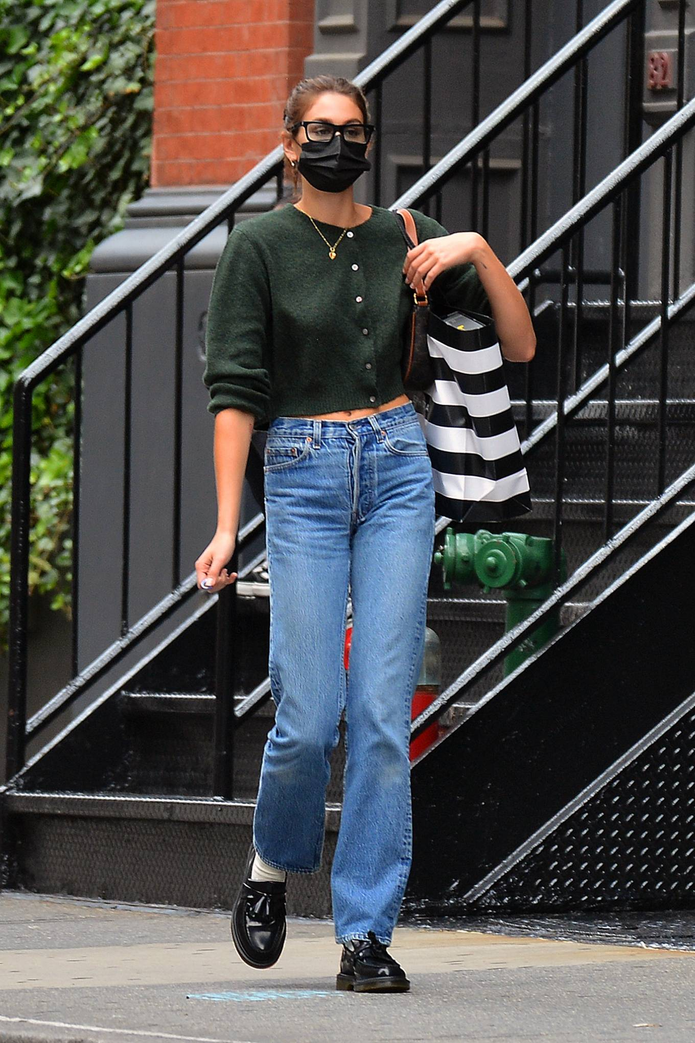 Kaia Gerber, Adrian boots, black boots, leather, black shoulder bag, olive green top, round, black sunglasses, blue jeans. Kaia Gerber rocking round black leather boots by Adrian