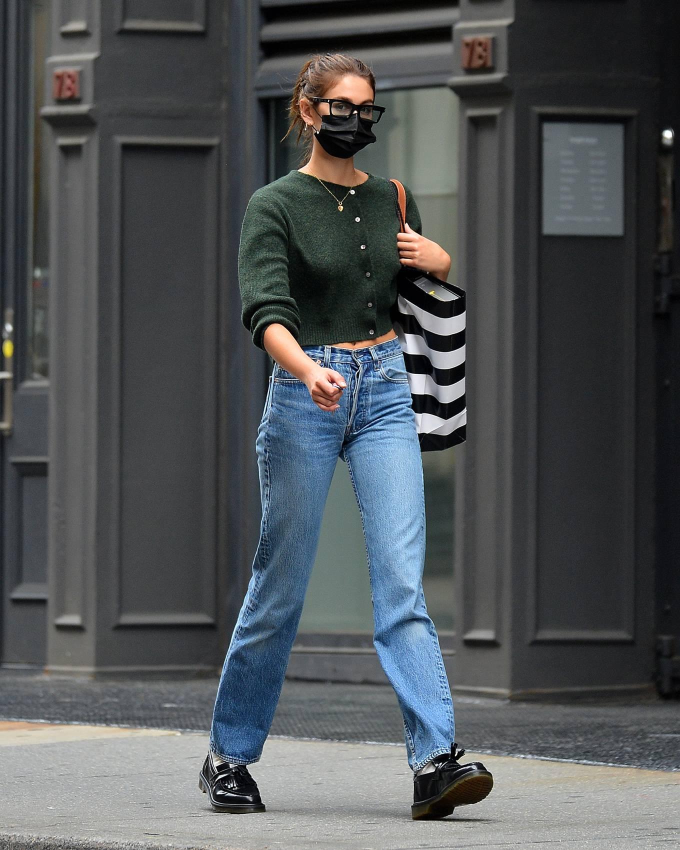 Kaia Gerber, black boots, leather, Adrian boots, black shoulder bag, olive green top, round, black sunglasses, blue jeans. Kaia Gerber rocking round black leather boots by Adrian