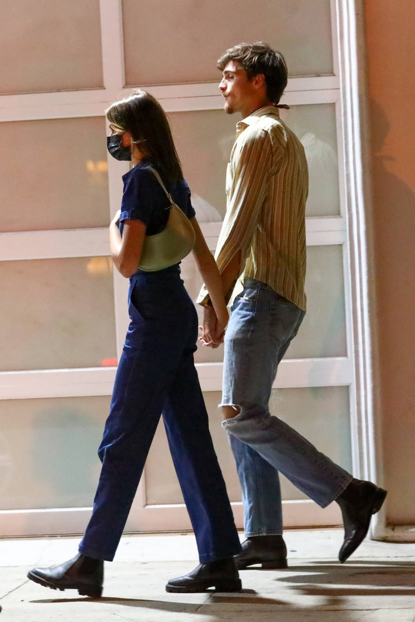 Kaia Gerber wearing a fitted navy blue jumpsuit with a denim material, short sleeves, shirt collar and side pockets