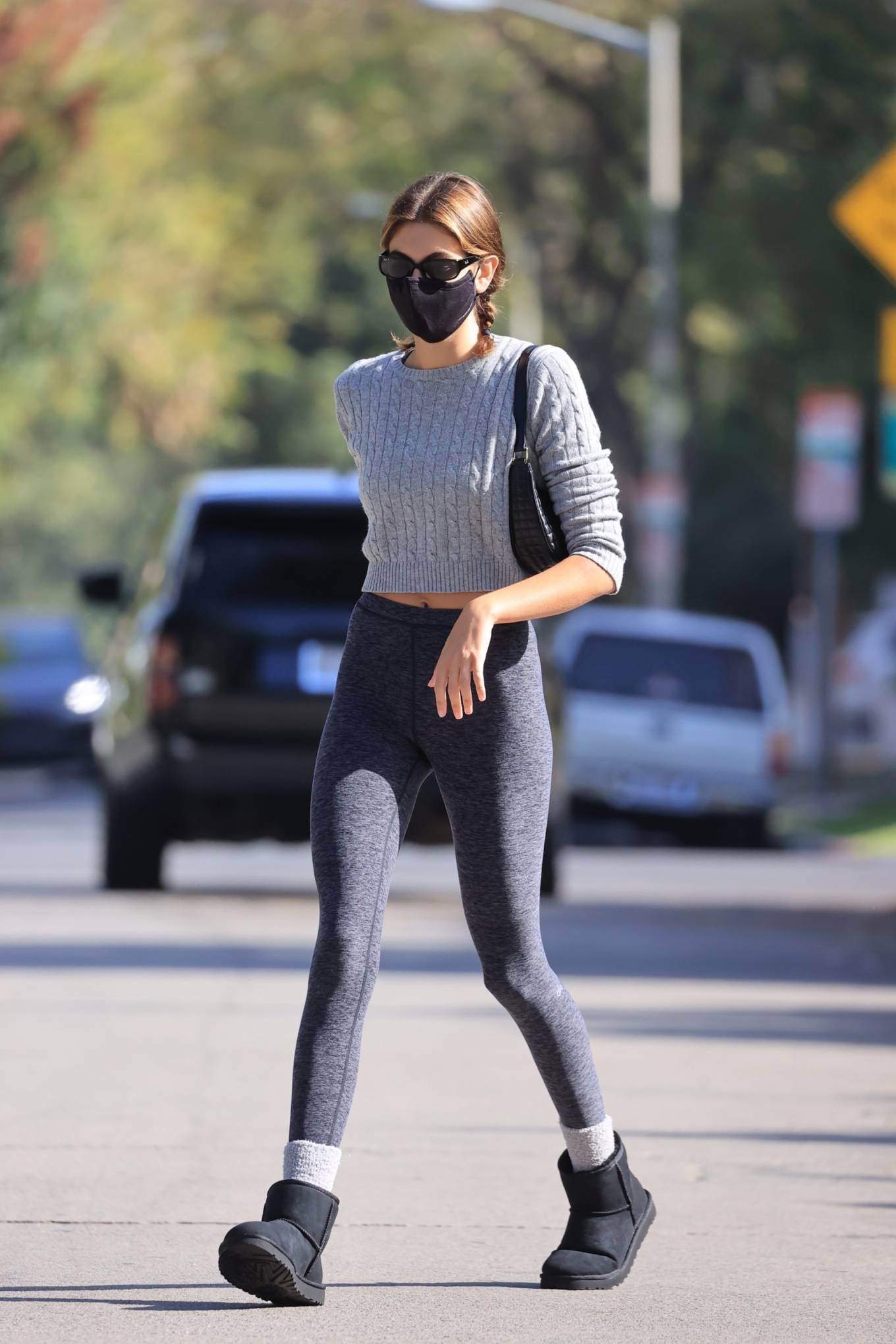 Kaia Gerber donning a fitted grey sweater with a woolen fabric, rolled sleeves, pattern and a crew neck