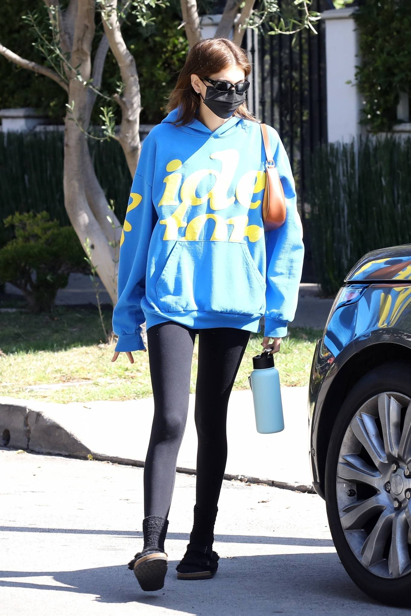 Kaia Gerber wearing round black slip on slippers by Birkenstock with wide strap