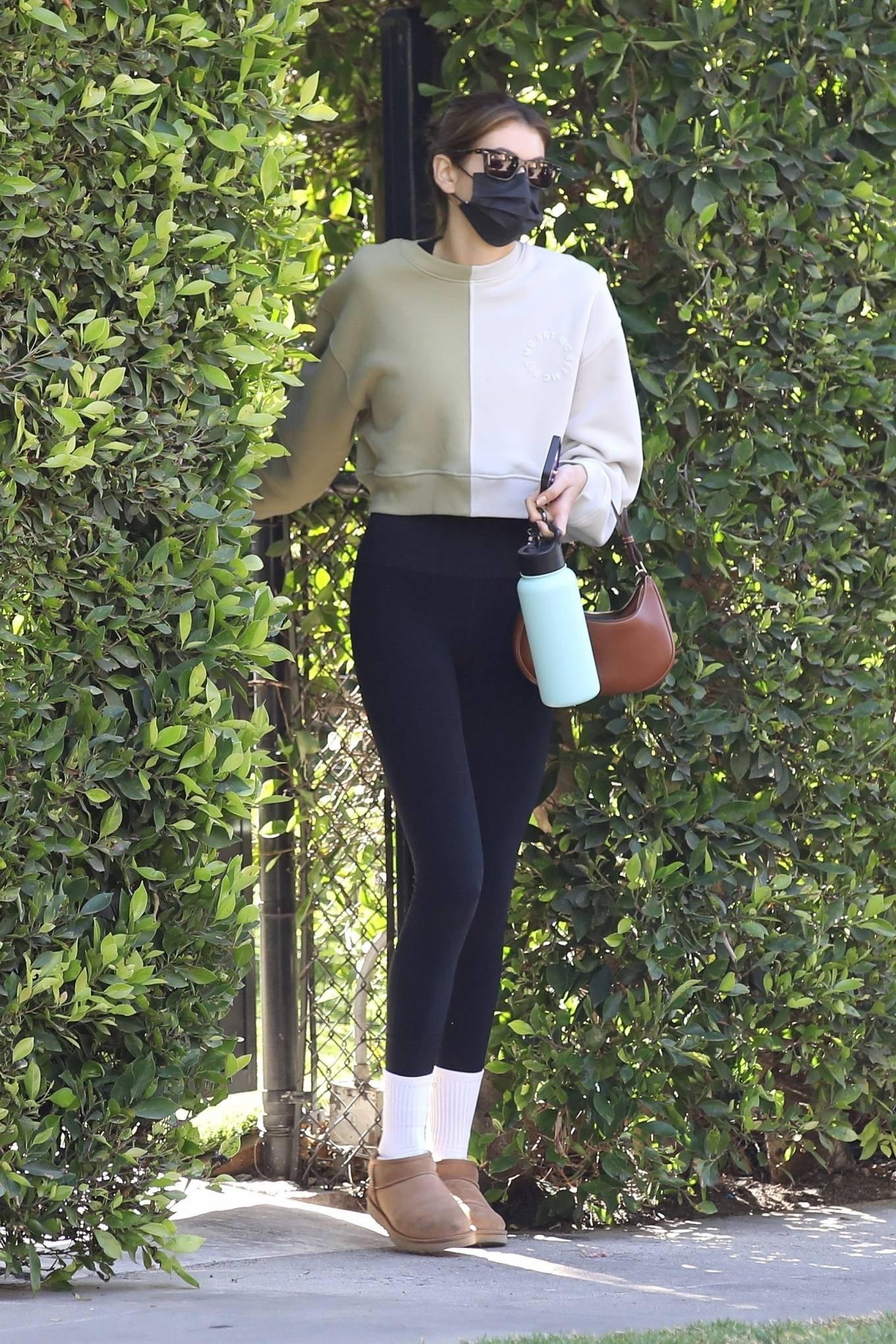 Kaia Gerber wearing skinny black high waist ankle length workout leggings with brand logo