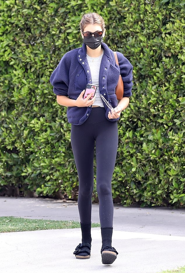 Kaia Gerber, black sandals, suede, Birkenstock sandals, oversized navy blue Free People Jacket, tan Celine shoulder bag, round, open toe, flat heel, grey top, brown sunglasses, two-strap, figure hugging black workout leggings. Kaia Gerber rocking round black suede open toe sandals by Birkenstock with flat heel