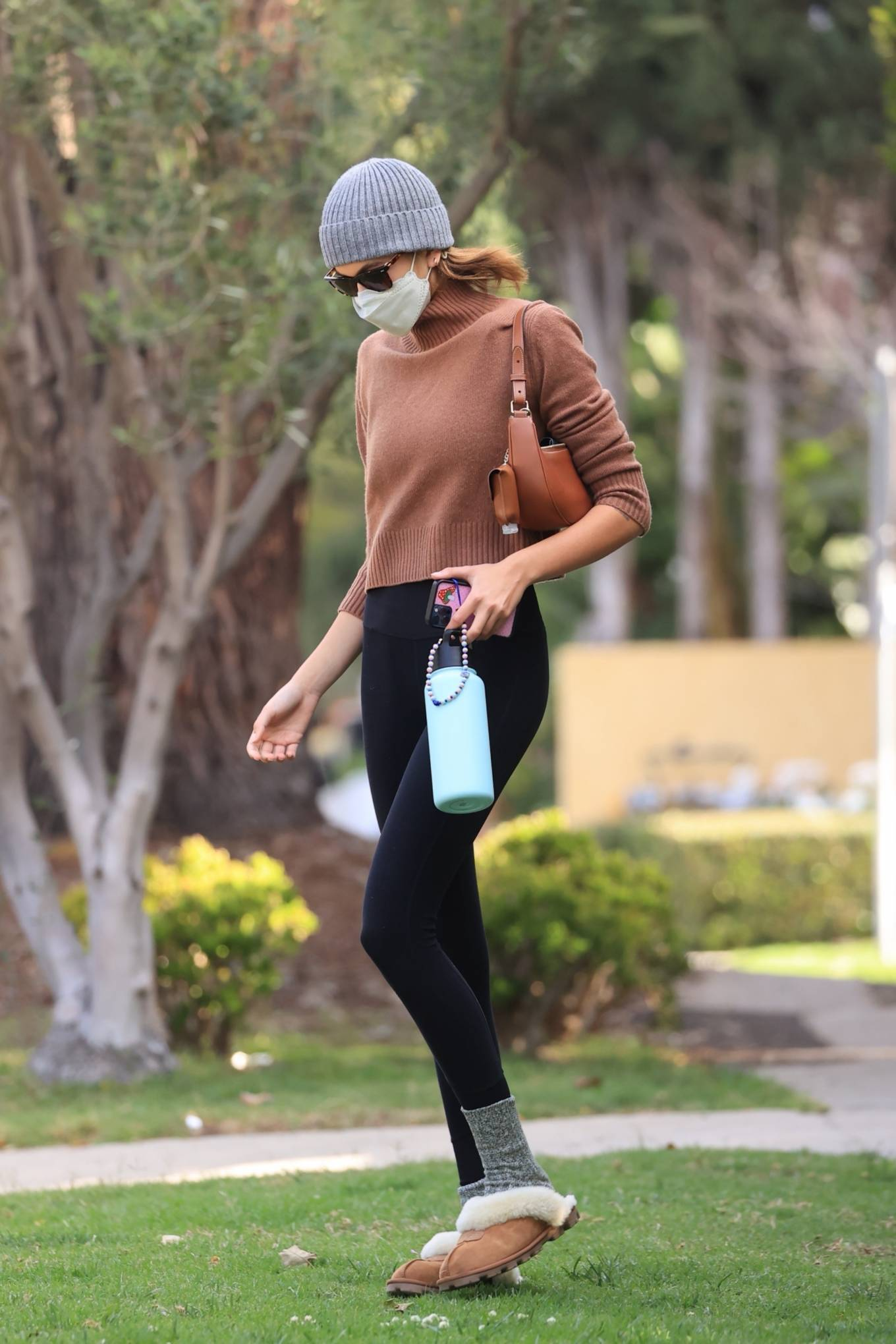 Kaia Gerber wearing round brown Ugg slip on slippers with flat heel