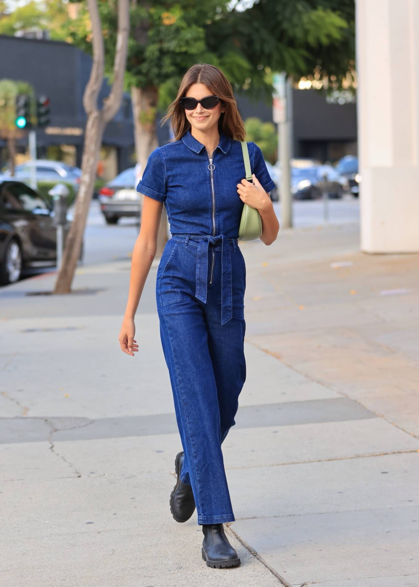 Kaia Gerber donning a fitted navy blue jumpsuit with a denim fabric, short sleeves, shirt collar and side pockets