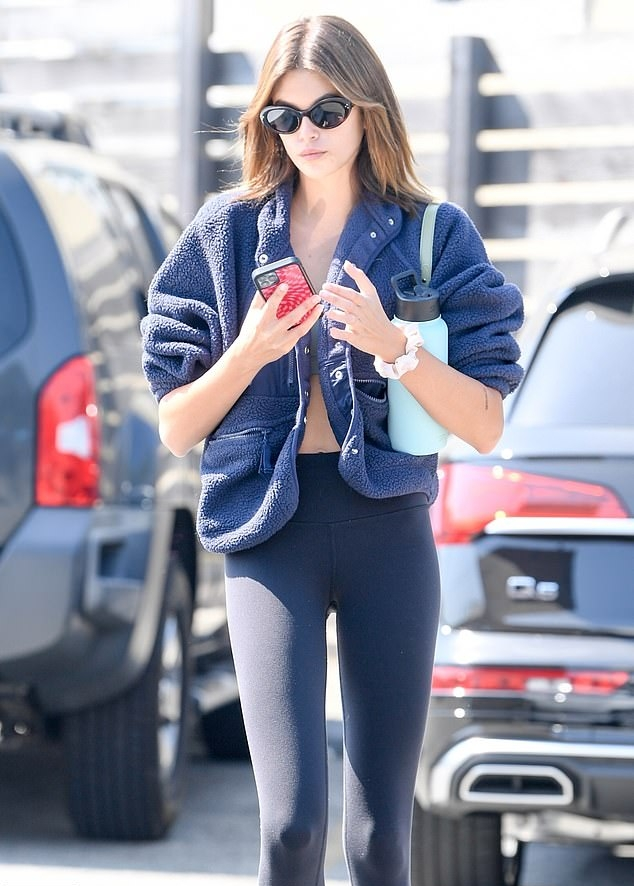 Kaia Gerber wearing fitted black side-striped ankle length workout leggings with high rise