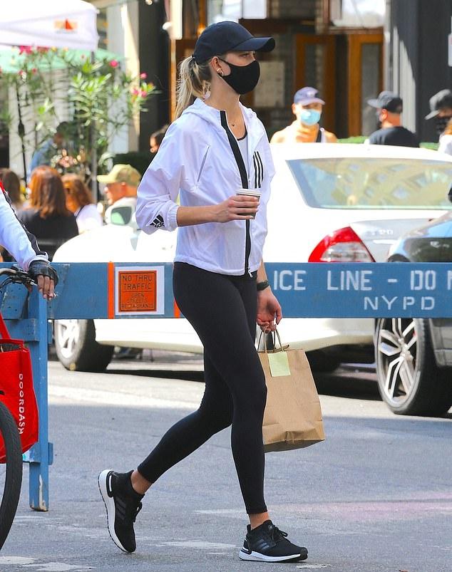 Karlie Kloss wearing black Adidas lace-up sneakers