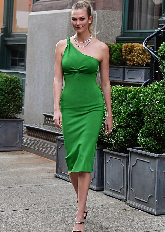 Karlie Kloss wearing a figure hugging green dress that showcased her model figure while out and about in New York