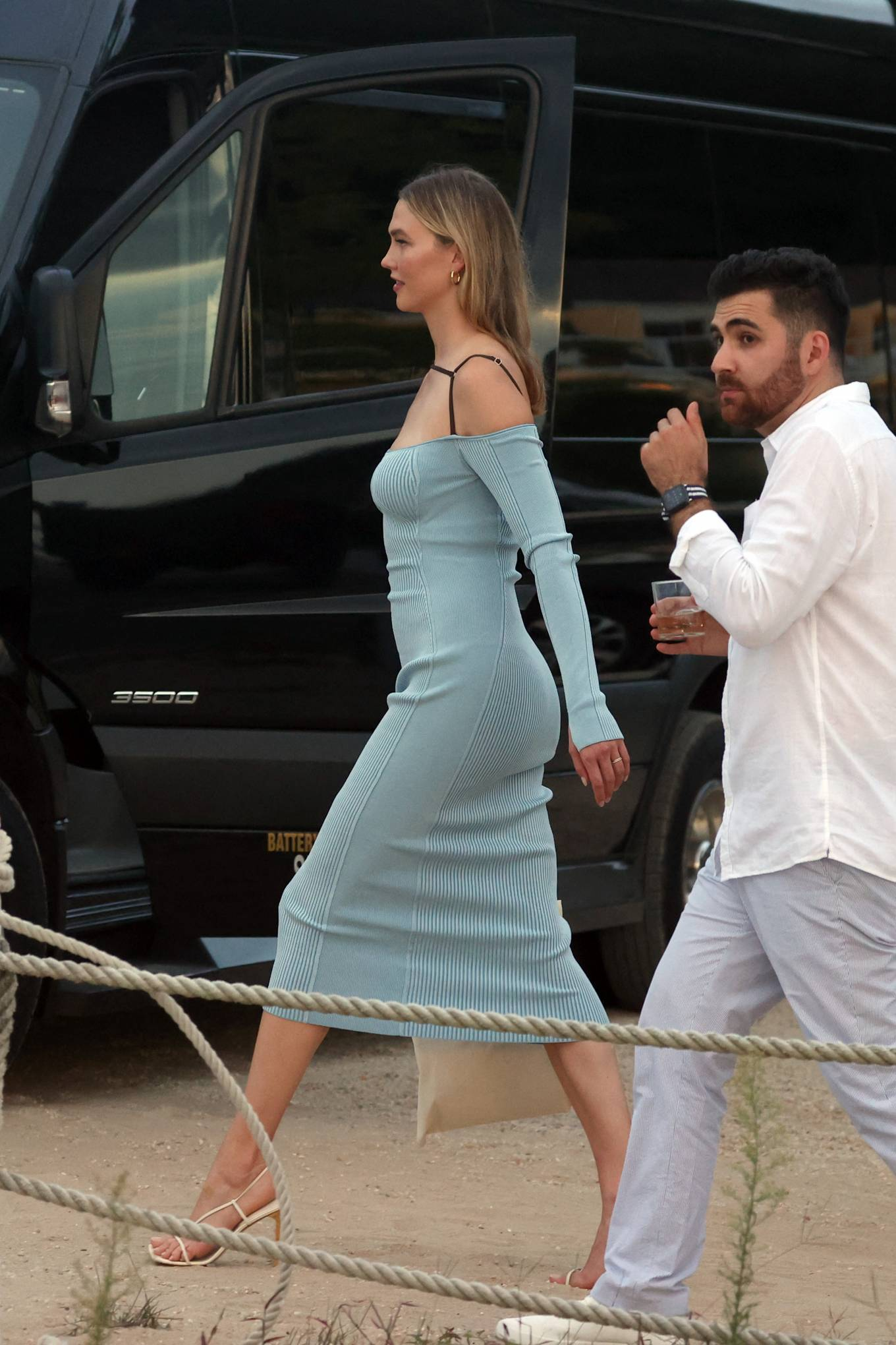 Karlie Kloss wearing a flattering light blue dress with a viscose fabric, full sleeves and cold shoulder