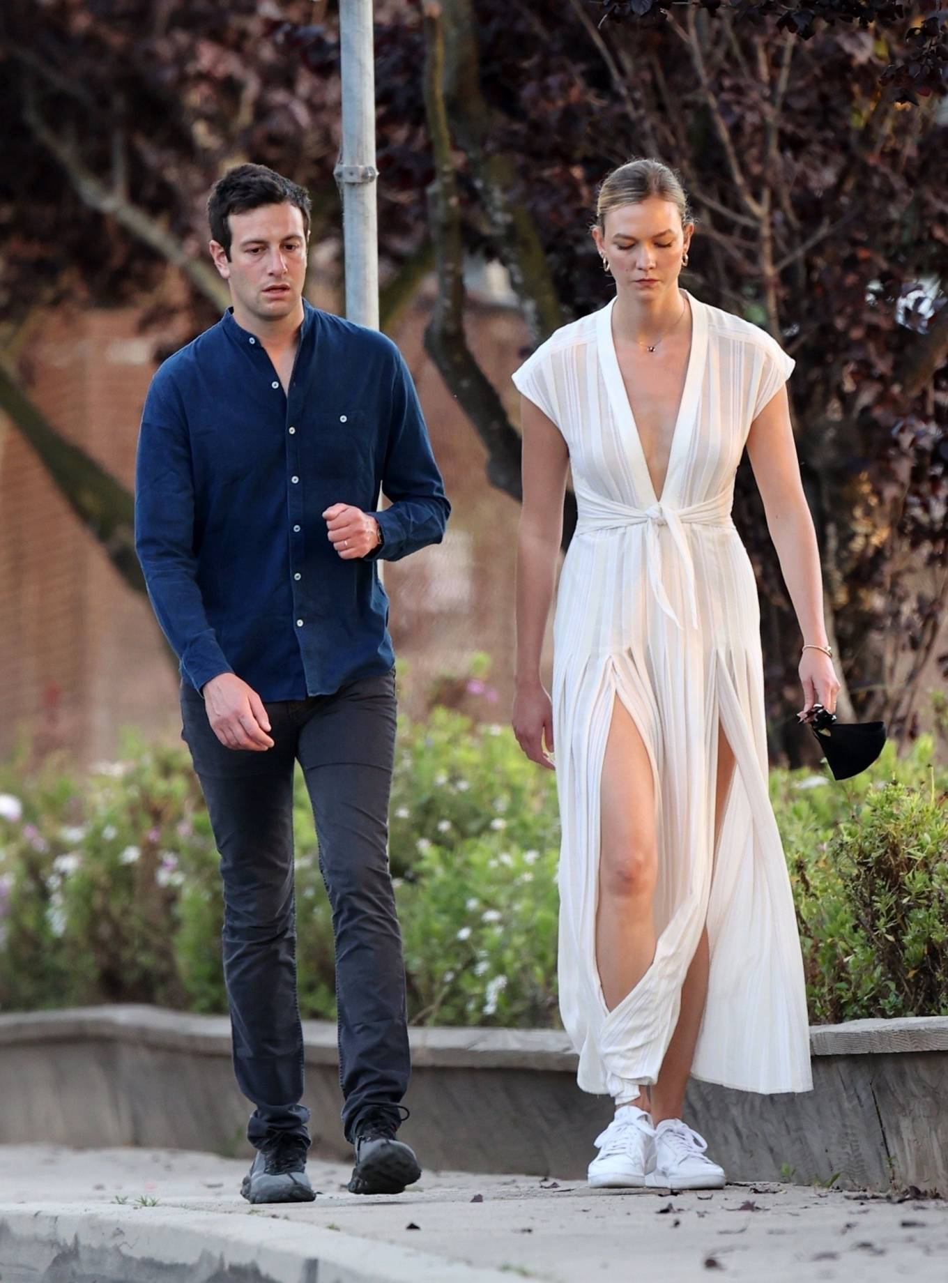 Karlie Kloss rocking a Sexy white pleated sexy slit maxi dress with cap sleeves, pleated, a V-neck and flared hem