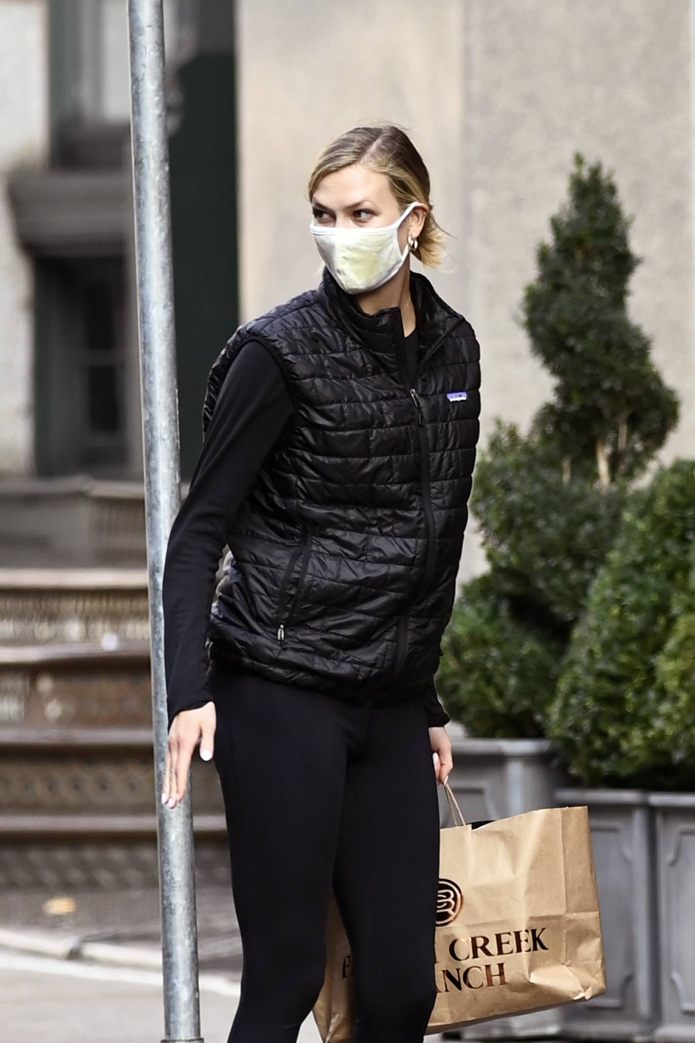 Karlie Kloss wearing white leather lace-up sneakers