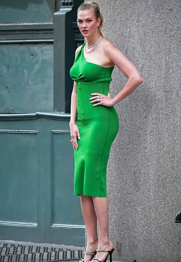 Karlie Kloss donning a figure hugging green dress with a knit material, one shoulder, ruched and a asymetrical neckline