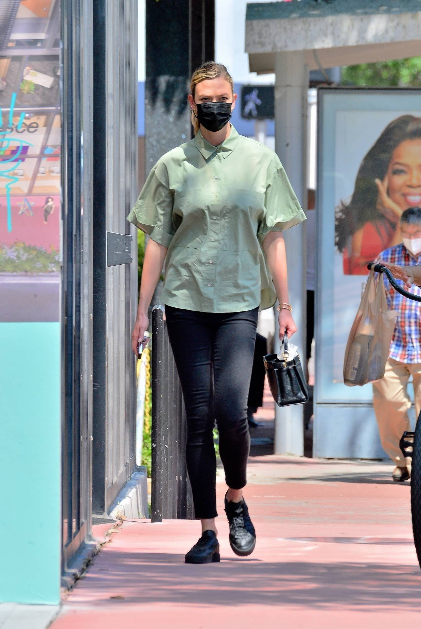 Karlie Kloss donning round black lace-up sneakers with flat heel