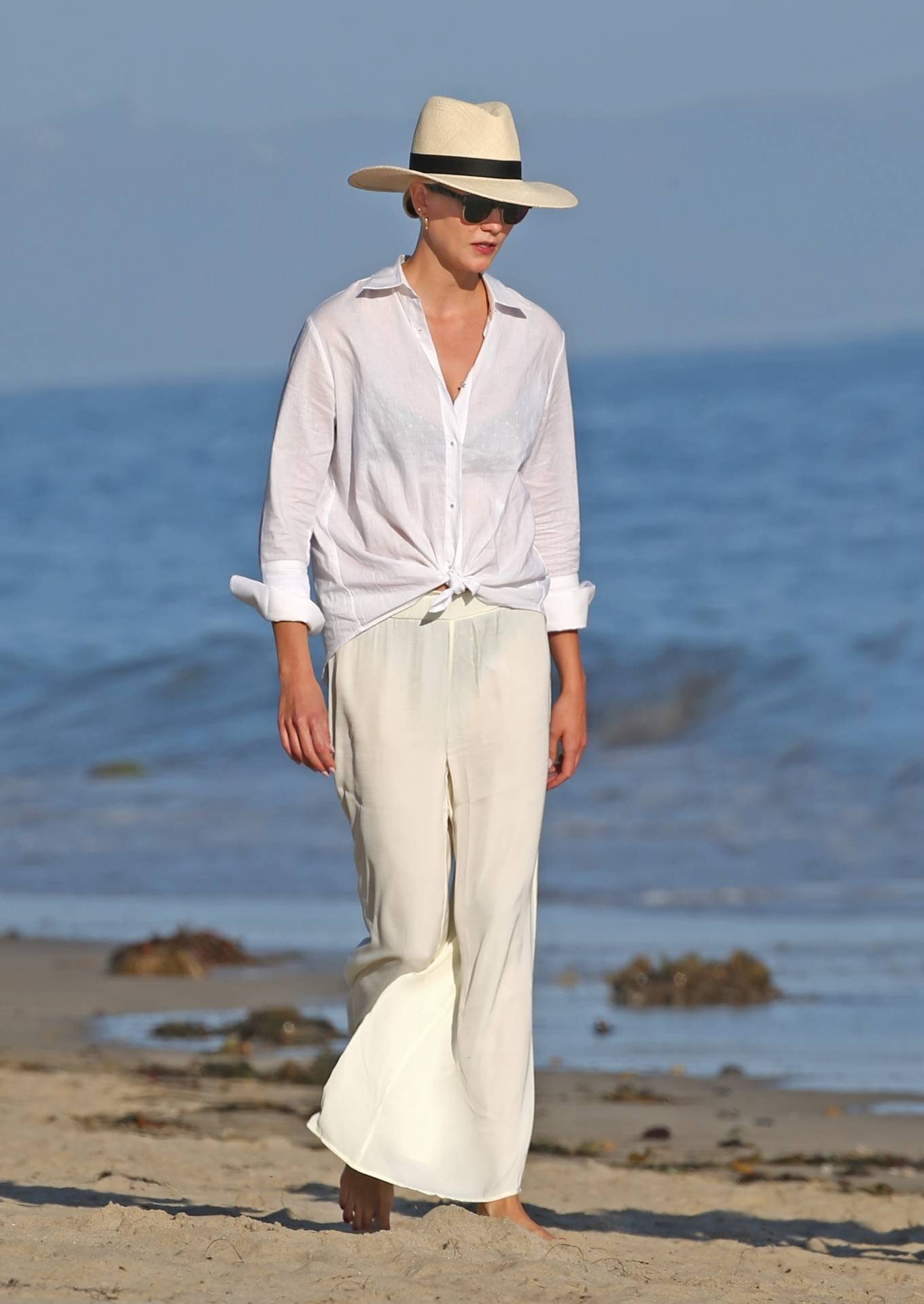 Karlie Kloss donning white straight fit trousers