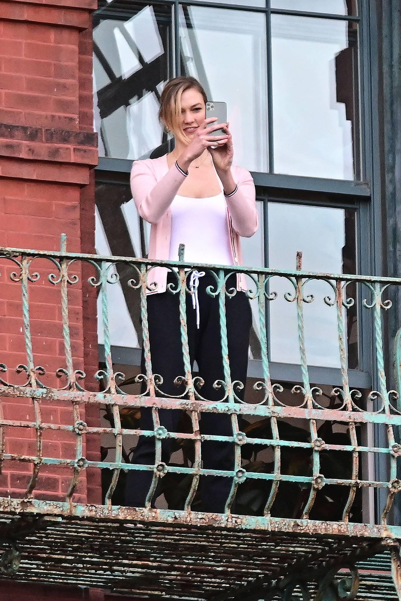 Karlie Kloss, black trousers, baby pink cardigan, high waist, slim fit, figure hugging white tank top. Karlie Kloss wearing Black high waist trousers