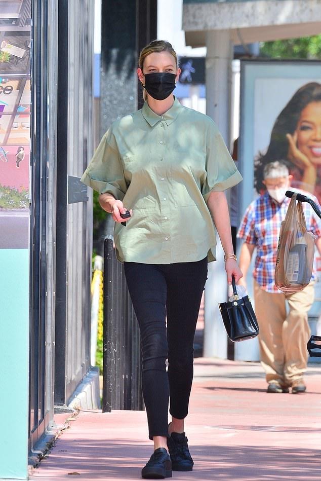 Karlie Kloss, black sneakers, black Fendi hand bag, mint green shirt, flat heel, round, lace-up, figure hugging black jeans. Karlie Kloss donning round black lace-up sneakers with flat heel