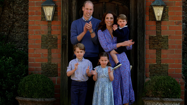 Kate Middleton wearing a Flowing Ghost floral midi dress with a satin material, puffy sleeves, puffed shoulder, peak lapel collar, floral print and flared hem