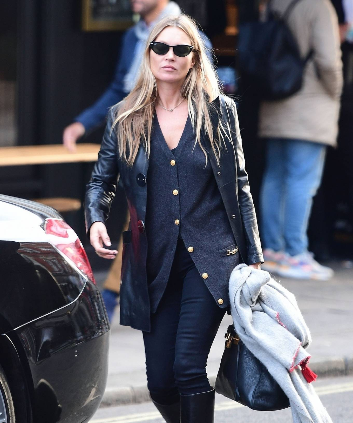 Kate Moss donning narrow black leather mid calf boots with high block heel