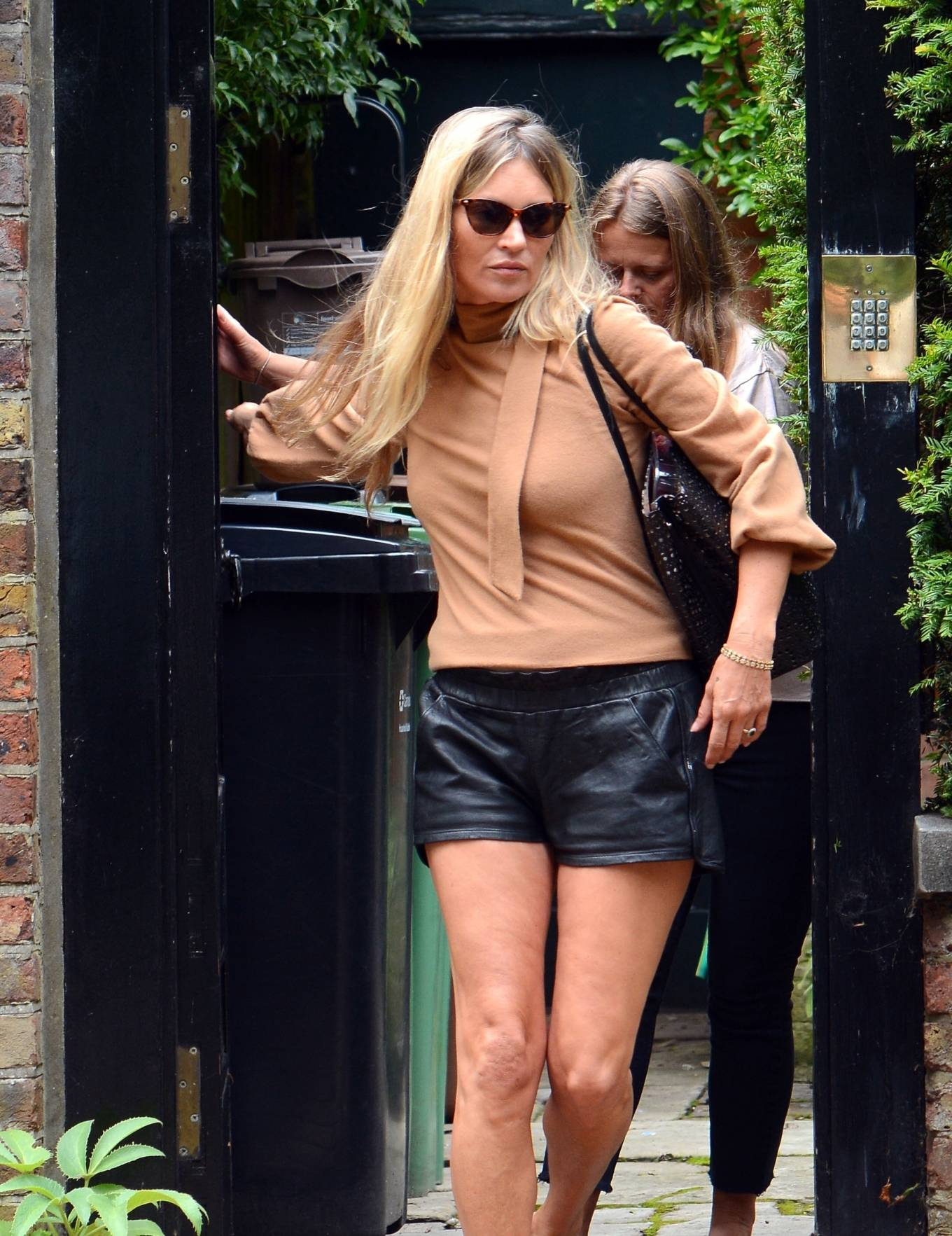 Kate Moss donning Skimpy black leather high rise shorts with side pockets and a leather fabric