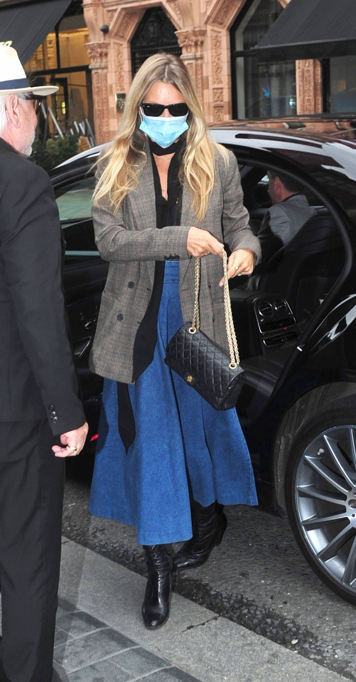 Kate Moss donning a black lace detailing shirt with a bow neck
