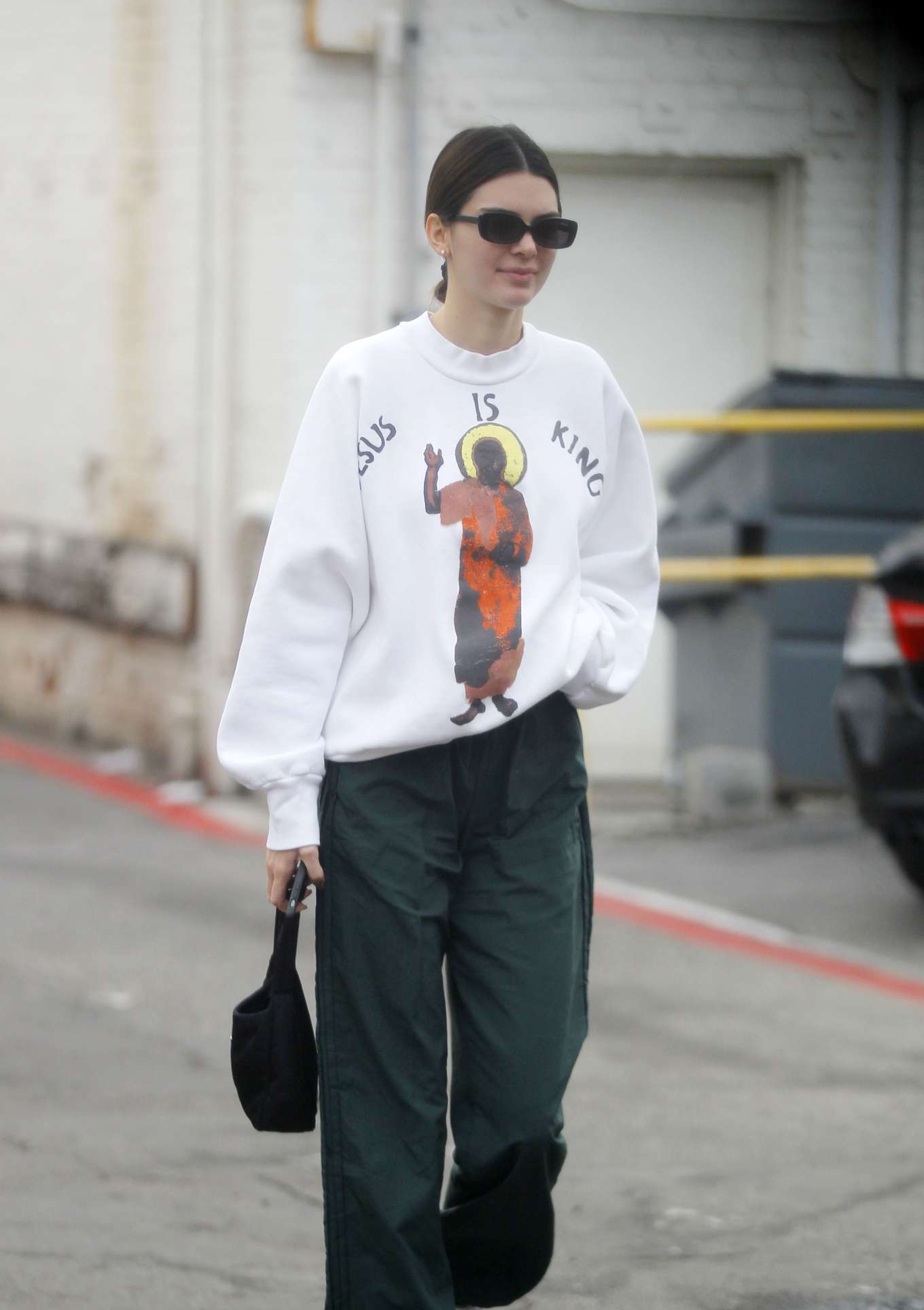 Kendall Jenner donning a Oversized white sweatshirt with a woolen fabric, extra long sleeves, wide cuffs, a crew neck and ribbed trim hem