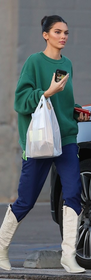 Kendall Jenner White pointy white leather cowboy boots by Forward Oversized green sweatshirt with relaxed fit navy blue side-striped track pants by Adidas