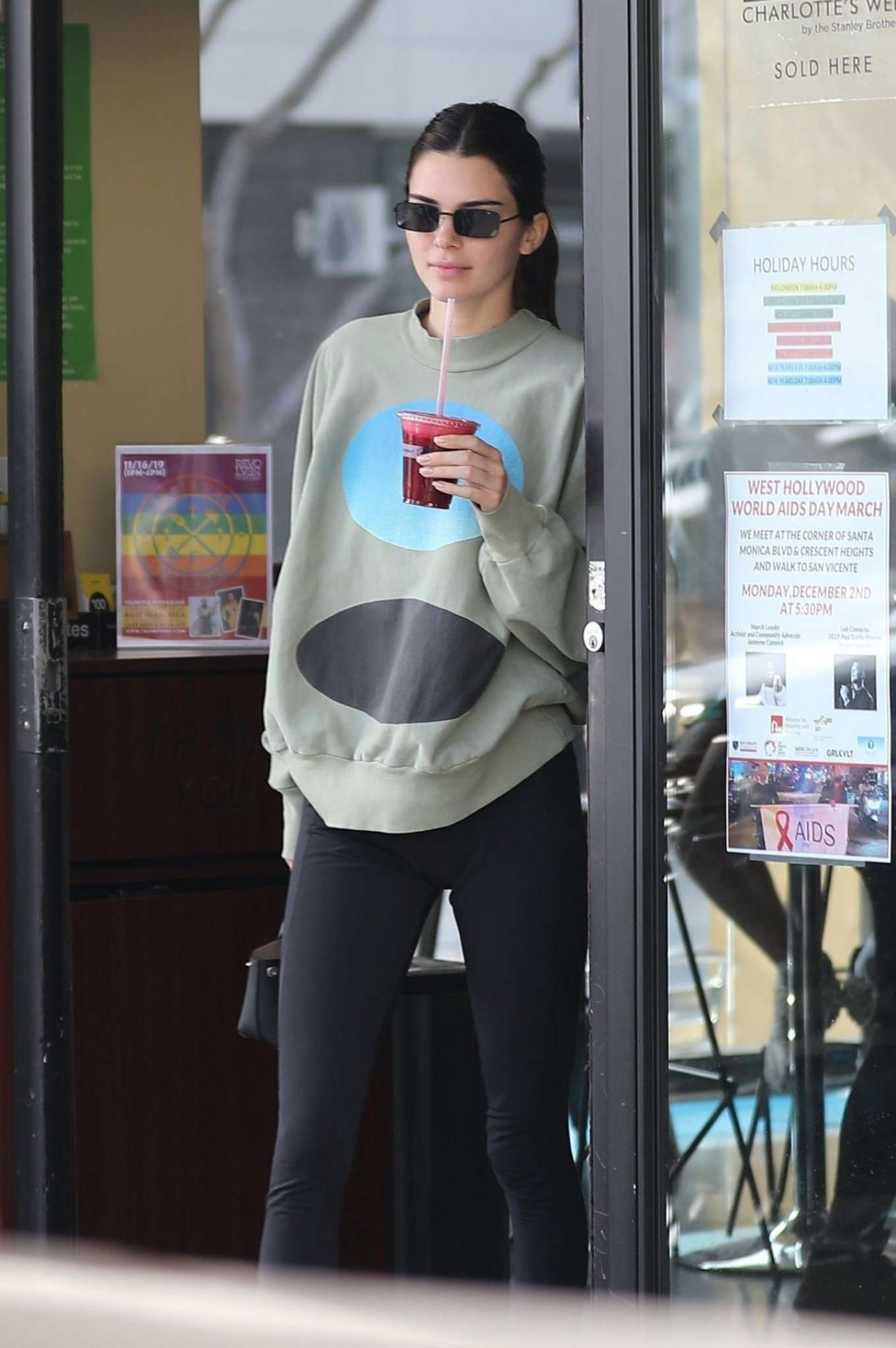Kendall Jenner donning chunky neon black green lace-up trainers