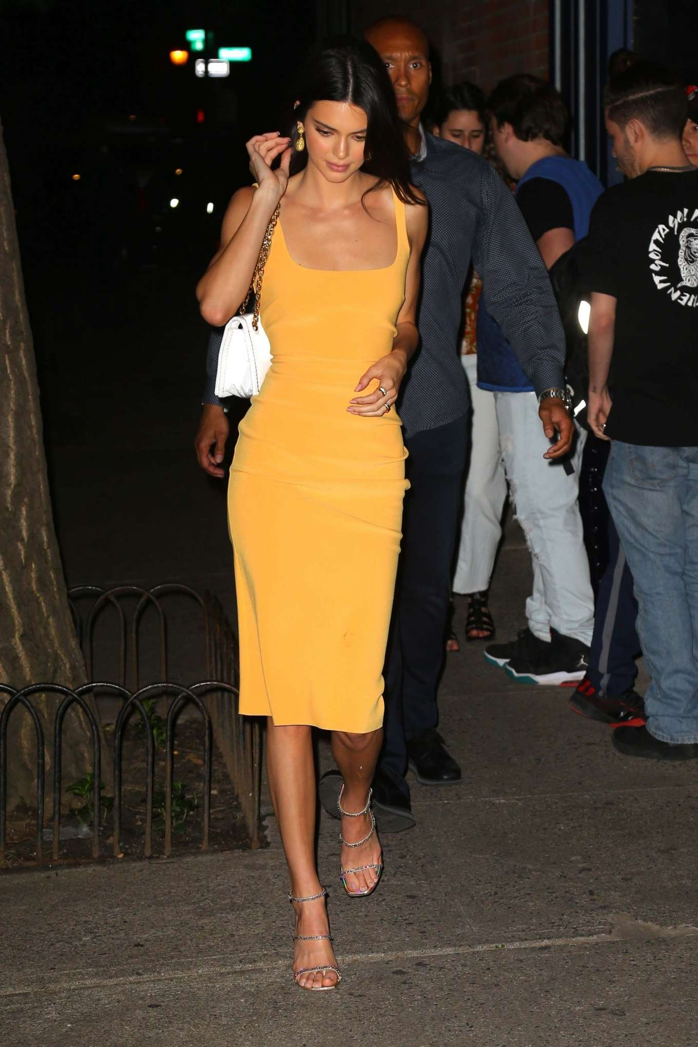 Kendall Jenner rocking a Figure hugging Light yellow midi dress with a scoop neck and straps
