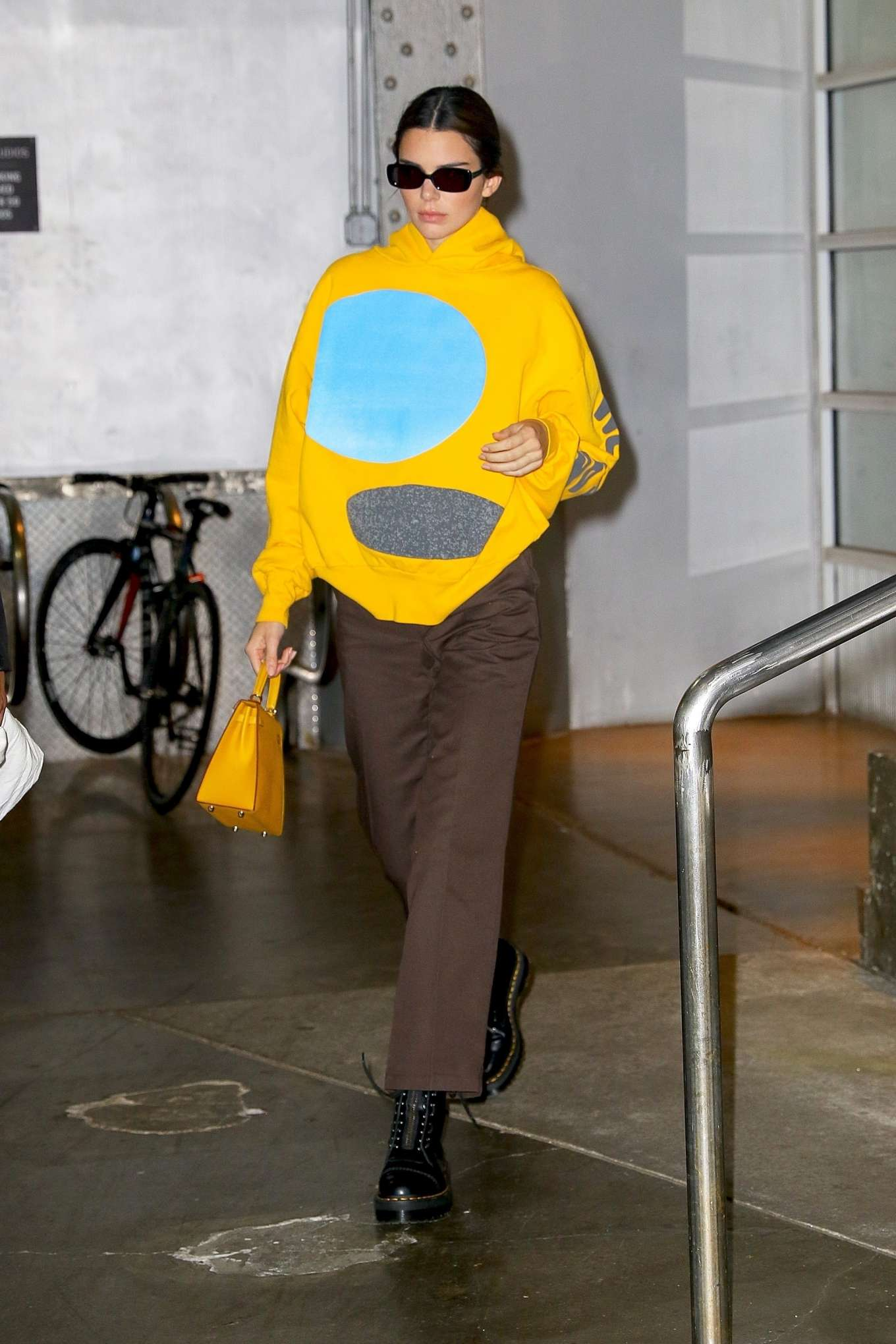 Kendall Jenner donning a Oversized Bright yellow hooded sweatshirt with full sleeves and a high neck