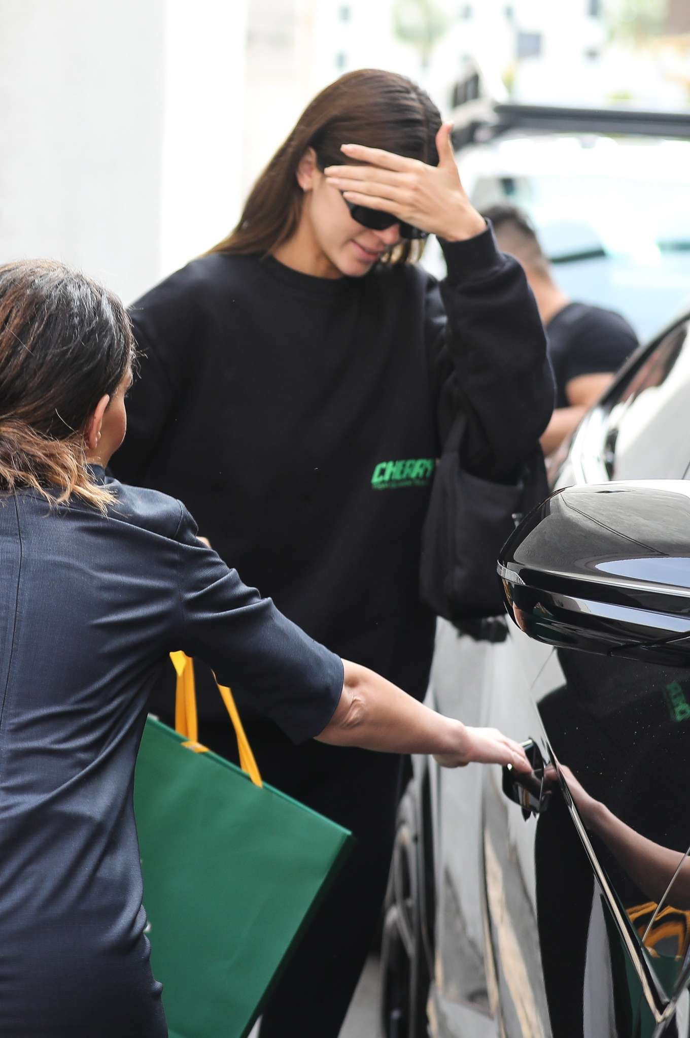 Kendall Jenner wearing a Oversized black sweatshirt with a woolen fabric, extra long sleeves, brand logo, a crew neck and ribbed trim hem