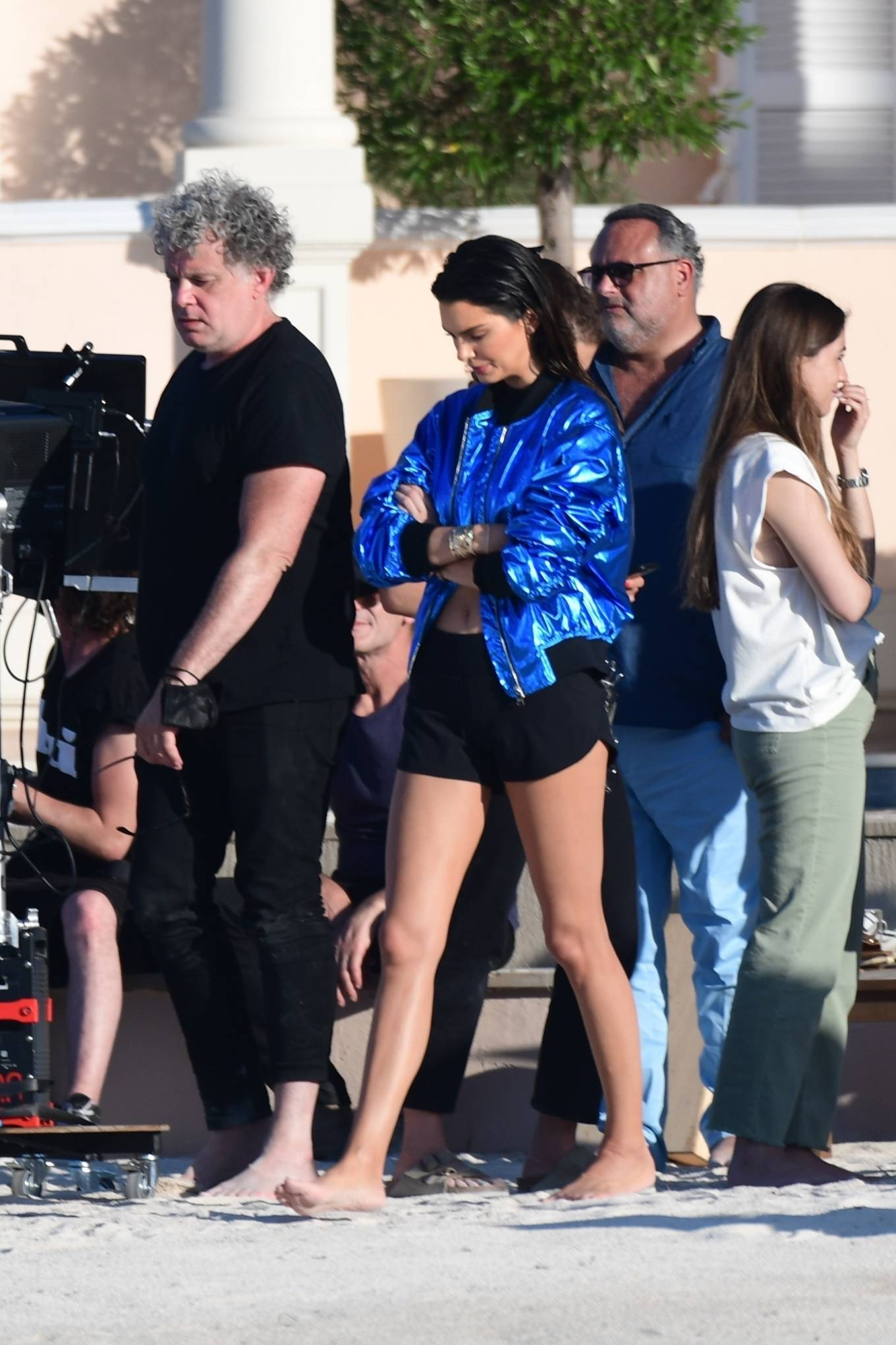 Kendall Jenner, blue jacket, black crop top, front zip, waist length, rolled sleeves, baseball collar, open front, black bikini bottom. Kendall Jenner wearing a metallic blue open front jacket with rolled sleeves and baseball collar