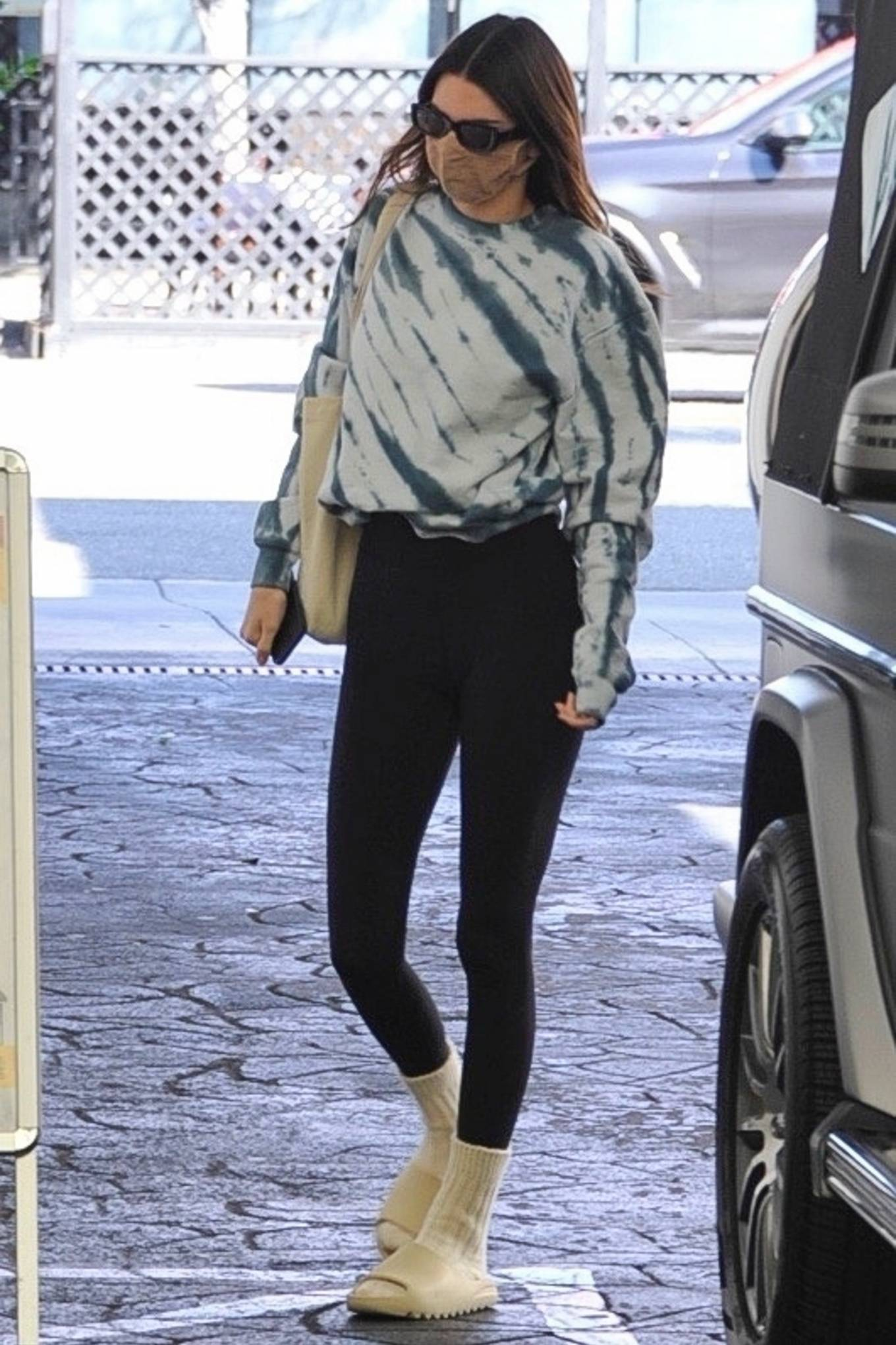 Kendall Jenner donning white(bone) Adidas x Yeezy slippers with chunky sole