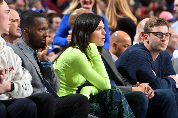 Kendall Jenner wearing a Figure hugging neon green sweater with a woolen material, extra long sleeves and a turtleneck