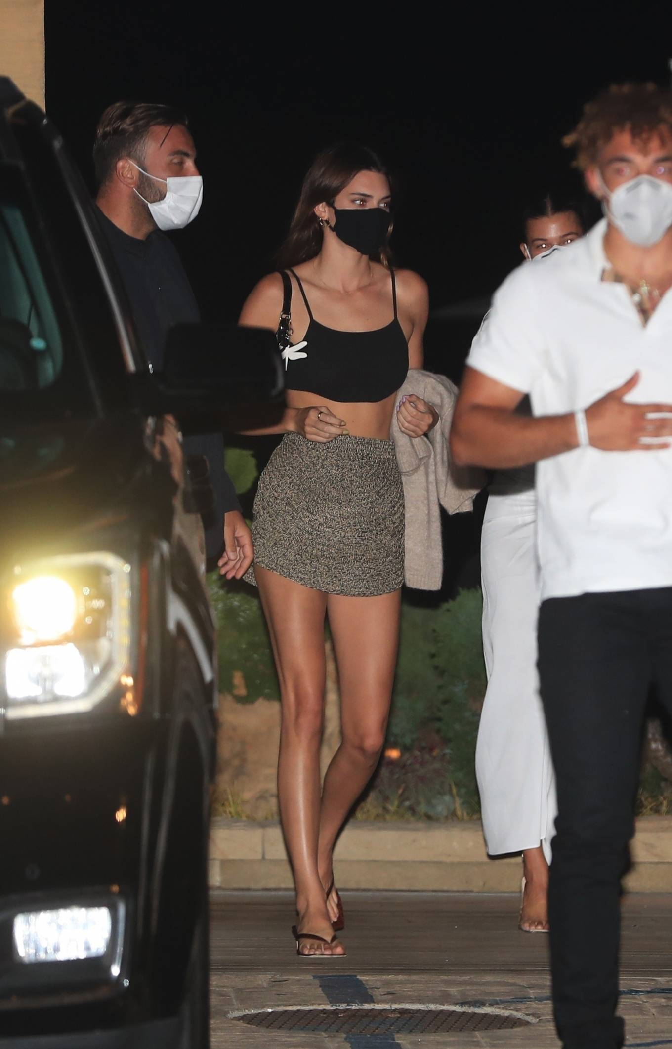 Kendall Jenner donning a Figure hugging Meshki black crop top with very thin spaghetti straps