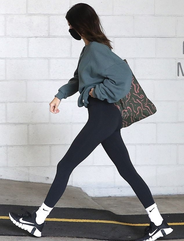 Kendall Jenner rocking a oversized dark blue sweatshirt with bell sleeves and a round neck