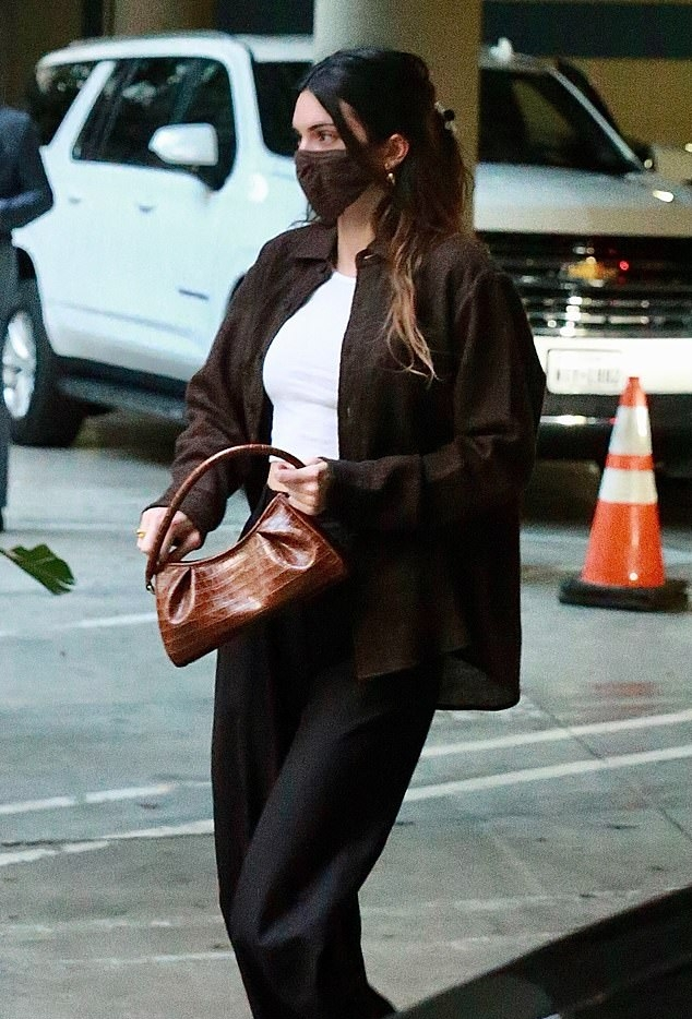 Kendall Jenner donning brand logo brown white lace-up sneakers by Nike with flat heel