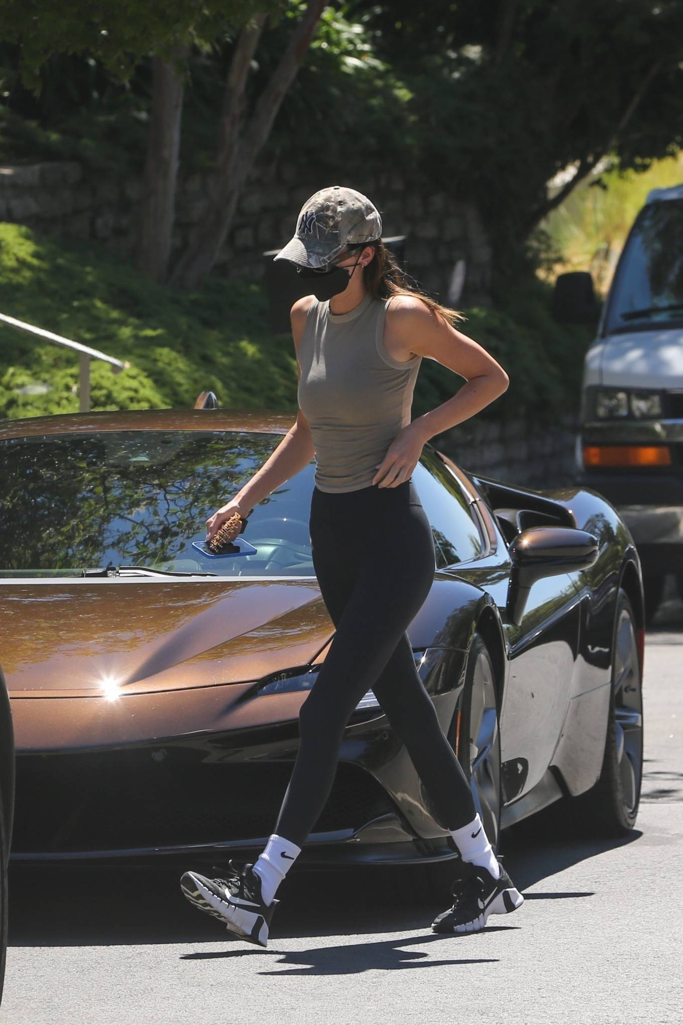 Kendall Jenner, grey top, cotton, SKIMS top, black and white Nike sneakers, black Nike workout leggings, waist length, sleeveless, crew neck, figure hugging, model figure, grey tank top, SKIMS tank top, rose gold Dmy by Dmy sunglasses, fitted, basic. Kendall Jenner donning a figure hugging grey tank top with a cotton fabric and a crew neck
