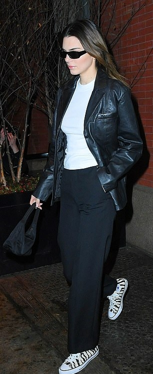 Kendall Jenner, leather, black jacket, white tee, white canvas shoes, relaxed fit, front zip, hip length, full sleeves, peak lapel collar, black pants, black Prada purse, black sunglasses. Kendall Jenner donning a relaxed fit black leather jacket with full sleeves and peak lapel collar